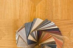 木地板不同的颜色样品在棕色木条地板背景的。 免版税库存照片