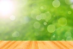 木地板和抽象绿色bokeh背景 免版税图库摄影