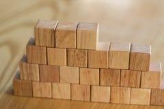 从木块修建的健壮的墙壁象征建筑和进展在大厦从混凝土或砖和创造 免版税库存图片