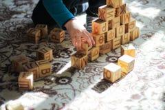 木块和儿童的休闲小男孩的概念金字塔使用在地板上的 库存照片