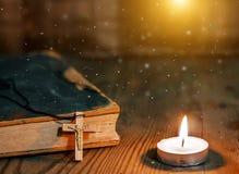 木基督徒十字架特写镜头在圣经,在老桌上的灼烧的蜡烛的 免版税库存照片