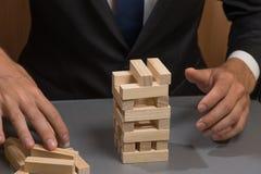 木塔式大楼,商人的手 风险和计划 免版税库存照片