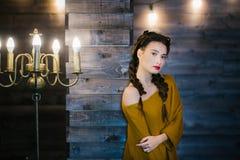 木墙壁的背景的女孩在大烛台附近的 免版税图库摄影