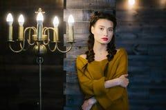 木墙壁的背景的女孩在大烛台附近的 免版税库存图片