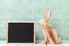 木复活节假日兔宝宝和一个空的黑板 免版税库存图片