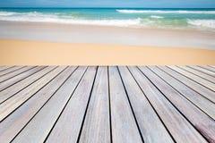 木大阳台有沙子海滩背景 库存图片