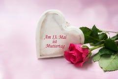 木头和一朵玫瑰的心脏在桃红色背景,德国文本上午1 免版税库存图片