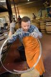 木头滚磨使用锤子和工具的生产木桶匠在车间 库存照片