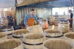 木头滚磨使用锤子和工具的生产木桶匠在车间 图库摄影