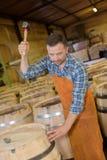 木头滚磨使用锤子和工具的生产木桶匠在车间 免版税库存图片