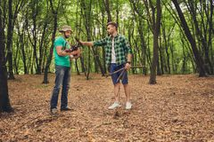 木头的两个年轻男性游人在秋天,收集木头为 库存图片