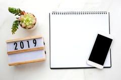 2019木头箱子,空白的笔记本纸,有空白的scre的巧妙的电话 库存照片