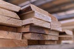 木头,没计划的杉木板被堆积在彼此顶部在金属机架 免版税库存照片