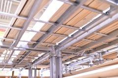 木头,没计划的杉木板被堆积在彼此顶部在金属机架 库存图片