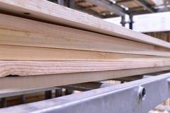 木头,没计划的杉木板被堆积在彼此顶部在金属机架 免版税库存图片