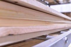 木头,没计划的杉木板被堆积在彼此顶部在金属机架 库存照片