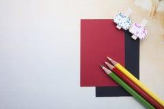 木夹子、稠粘的笔记和颜色铅笔 免版税库存照片
