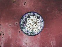 木字母表在金属表面上的一个玻璃瓶子成串珠状 库存照片