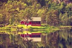 木客舱在湖岸的,挪威森林里 库存图片