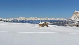 木客舱小屋在冬天dolimites雪山背景中 库存图片