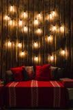 木室在有木墙壁和设计师电灯泡的,位子的装饰的地方土气房子里 红色灰色枕头 库存图片