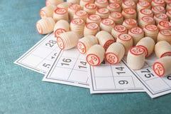 木小桶和卡片一个乐透纸牌的在绿色背景 免版税库存照片
