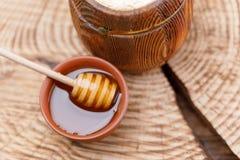 木小桶用蜂蜜和蜂蜜匙子在黏土碗在一把木锯 纬向条花 免版税图库摄影