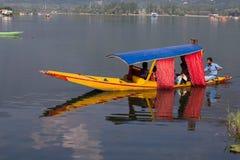 木小船和印地安人民在湖 斯利那加,印度 库存图片