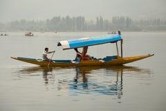 木小船和印地安人民在湖 斯利那加,印度 库存照片