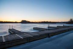 木小船看法在冻湖靠码头在日落 免版税库存图片
