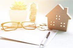 木屋模型、储蓄存款书或者财政决算和硬币在办公桌桌上 免版税库存图片