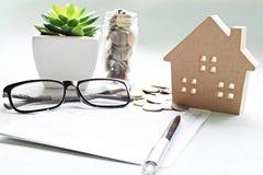 木屋模型、储蓄存款书或者财政决算和硬币在办公桌桌上 库存图片