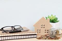 木屋模型和硬币从在办公桌桌上的玻璃瓶子驱散了 免版税库存图片