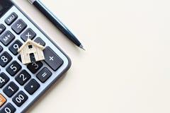 木屋模型和计算器在办公桌桌上 免版税库存图片