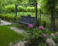 木庭院摇摆在有桃红色花的一个绿色庭院里 免版税库存图片