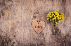 木心脏和黄色花在老被佩带的木背景 背景和纹理 复制空间 库存图片
