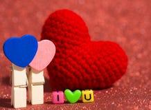 木心脏夹子有红色毛线心脏的和我爱你从小珠五颜六色在红色地板和背景上 复制文本的空间 库存图片
