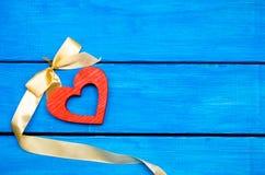 木心脏wwooden与一把弓的心脏在蓝色背景,华伦泰` s天 言情装饰 惊奇 免版税图库摄影