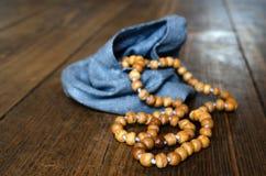 木念珠 在一个蓝色袋子的木念珠在一个木地板上 免版税库存照片