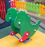 木恐龙春天跷跷板在孩子操场 库存图片