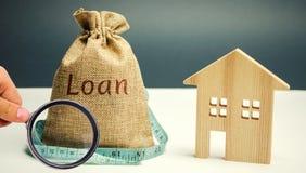 木房子和一个袋子与词贷款和卷尺 r 在不动产和风险的家庭投资 库存照片