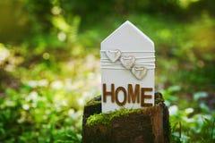 木房子在一个绿色森林和平家、自然、eco或者环境保护概念的一个树桩站立 图库摄影
