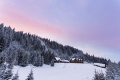 木房子在冬天多雪的森林里 免版税库存图片