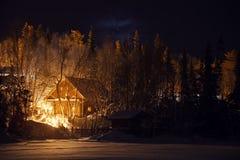 木房子在多雪的森林里在冬天晚上 免版税图库摄影