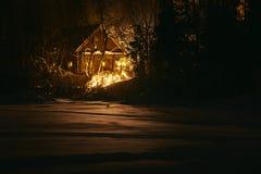 木房子在多雪的森林里在冬天晚上 免版税库存照片