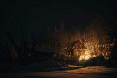 木房子在多雪的森林里在冬天晚上 免版税库存图片