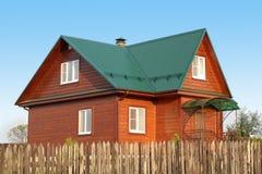 木房子在有白色塑料窗口的绿色金属屋顶下与百叶窗 免版税库存图片
