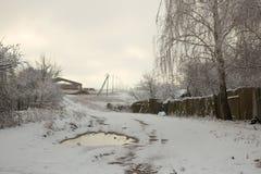木房子在有篱芭的一个村庄在雪下 免版税图库摄影