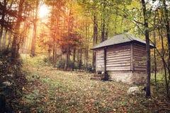 木房子在森林里,早期的秋天季节 免版税库存照片