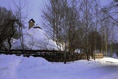 木房子在雪盖帽下的一个冬天森林里 免版税库存图片